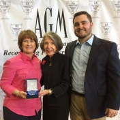 Kim Kincer (l) and Tyler Caviness (r) receive the Association of Golf Merchandis